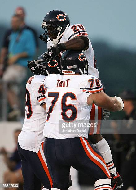 Running back Thomas Jones of the Chicago Bears is lifted by teammates John Tait and Jack Hunt after scoring a touchdown against the Miami Dolphins...