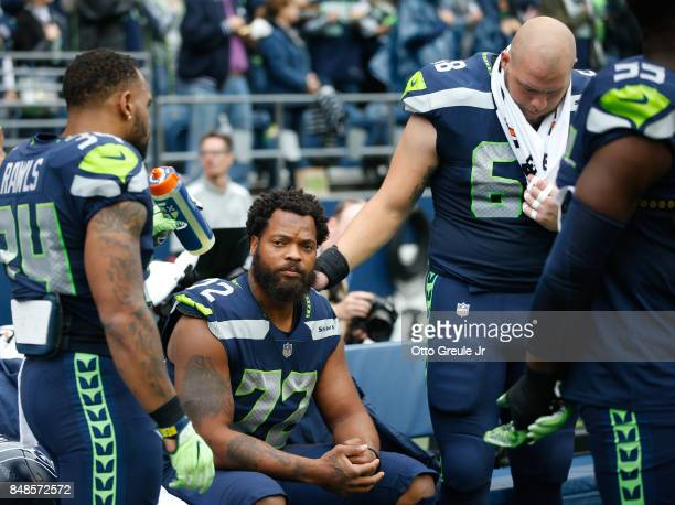 Running back Thomas Rawls of the Seattle Seahawks stands with center Justin Britt right to join defensive end Michael Bennett on the bench during the...