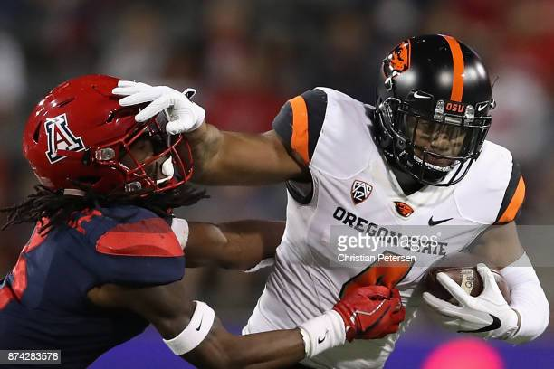 Running back Thomas Tyner of the Oregon State Beavers rushes the football past safety Jarrius Wallace of the Arizona Wildcats during the second half...