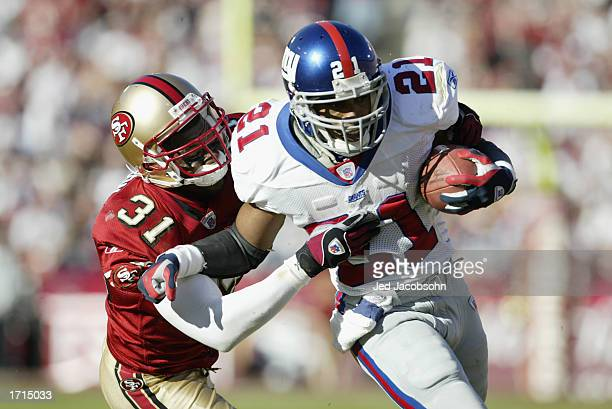 Running back Tiki Barber of the New York Giants runs against safety Zack Bronson of the San Francisco 49ers during the NFC Wild Card Game at...