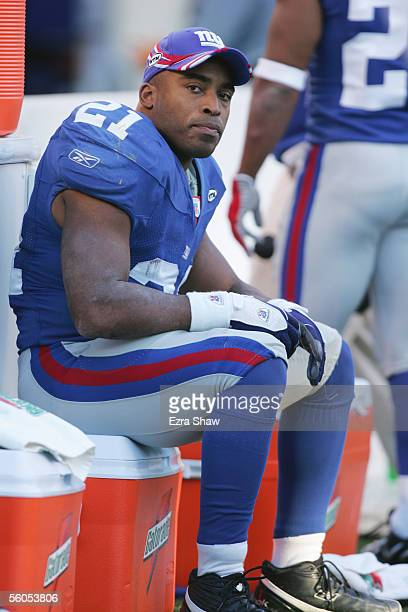 Running back Tiki Barber of the New York Giants sits on the sideline against the Washington Redskins at Giants Stadium on October 30 2005 in East...