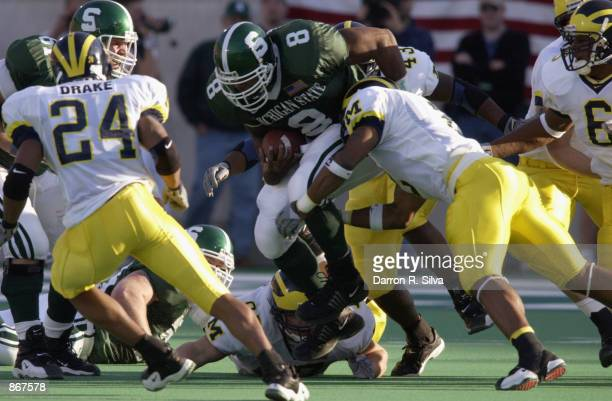 Running back TJ Duckett of the Michigan State Spartans vaults over a defender during the Big Ten Conference football game against the Michigan...