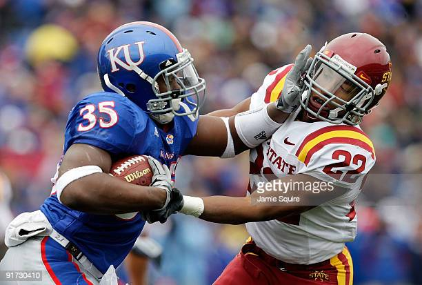 Running back Toben Opurum of the Kansas Jayhawks stiffarms Ter'ran Benton of the Iowa State Cyclones during the game on October 10, 2009 at Memorial...