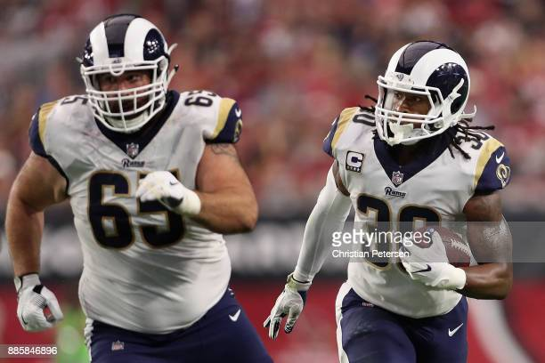 Running back Todd Gurley of the Los Angeles Rams ruhses the football alongside center John Sullivan during the NFL game against the Arizona Cardinals...