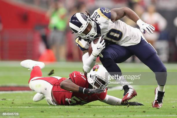 Running back Todd Gurley of the Los Angeles Rams runs past linebacker Josh Bynes of the Arizona Cardinals during the first half of the NFL game at...