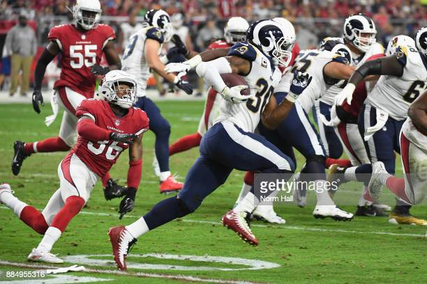 Running back Todd Gurley of the Los Angeles Rams runs past safety Budda Baker of the Arizona Cardinals during the first half of the NFL game at the...