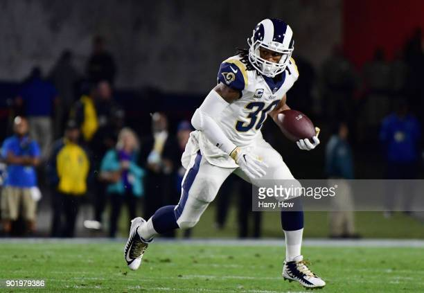 Running back Todd Gurley of the Los Angeles Rams runs with the ball after taking a hand off during the first quarter of the NFC Wild Card Playoff...
