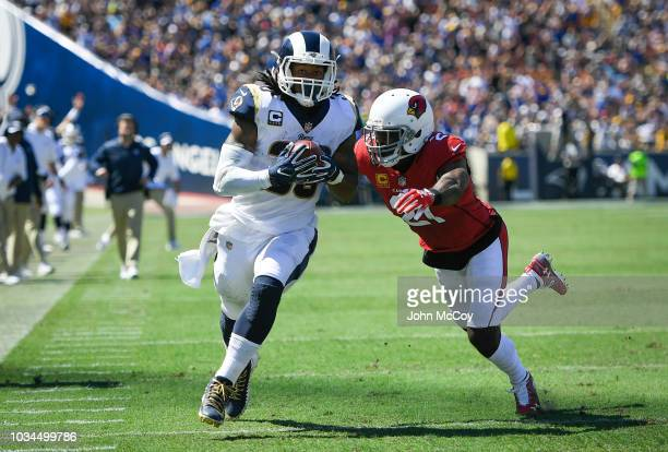 Running back Todd Gurley of the Los Angeles Rams scores a touchdown avoiding defensive back Patrick Peterson of the Arizona Cardinals in the second...