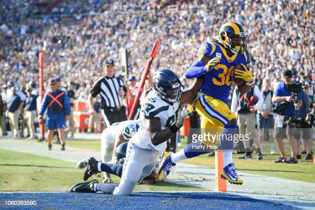 Running back Todd Gurley of the Los Angeles Rams scores a touchdown in front of defensive end Dion Jordan of the Seattle Seahawks to take a 1714 lead...