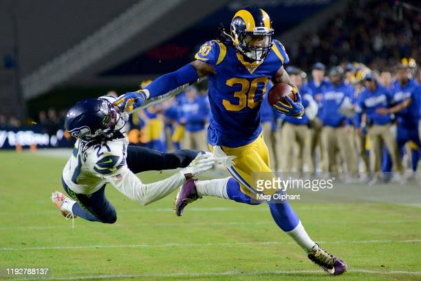 Running back Todd Gurley of the Los Angeles Rams stiff arms cornerback Tre Flowers of the Seattle Seahawks on his way to a touchdown in the fourth...