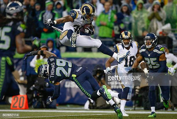 Running back Todd Gurley of the St Louis Rams rushes against free safety Earl Thomas of the Seattle Seahawks at CenturyLink Field on December 27 2015...