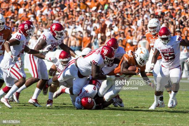 running back Toneil Carter of the Texas Longhorns is tackled by defensive tackle Neville Gallimore of the Oklahoma Sooners during the Oklahoma...