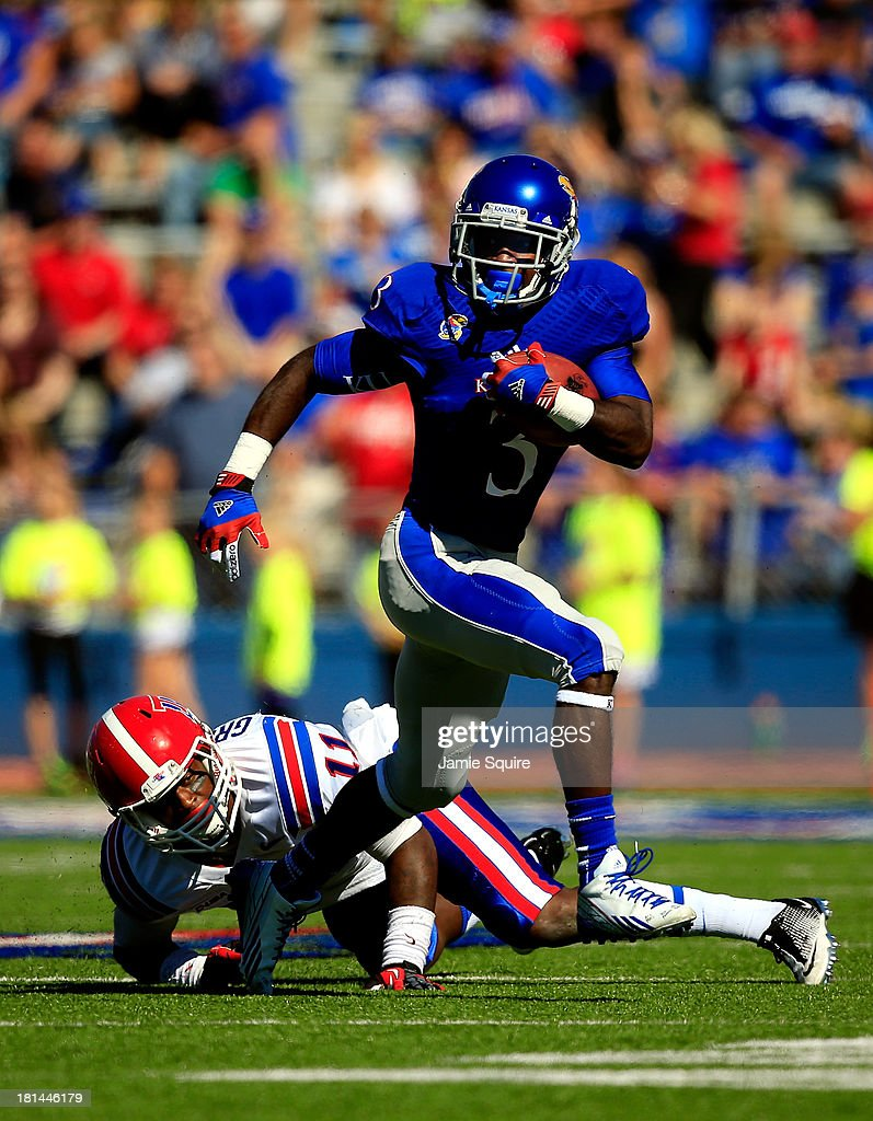 Running back Tony Pierson #3 of the Kansas Jayhawks breaks a tackle and carries the ball past defensive back Lloyd Grogan #11 of the Louisiana Tech Bulldogs during the game at Memorial Stadium on September 21, 2013 in Lawrence, Kansas.