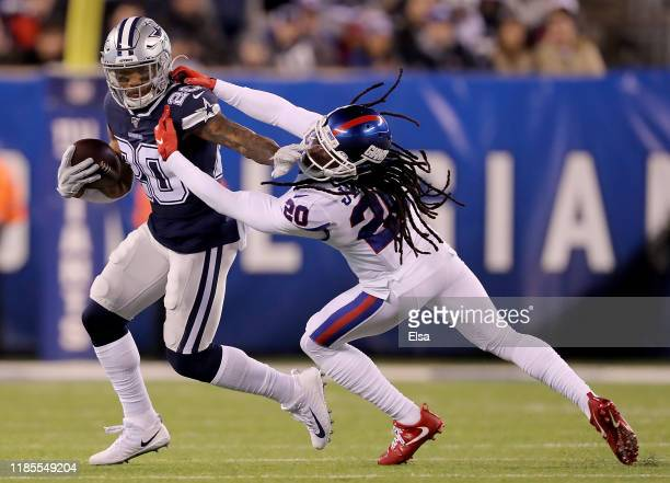 Running back Tony Pollard of the Dallas Cowboys breaks free of the defense of cornerback Janoris Jenkins of the New York Giants to carry for a first...