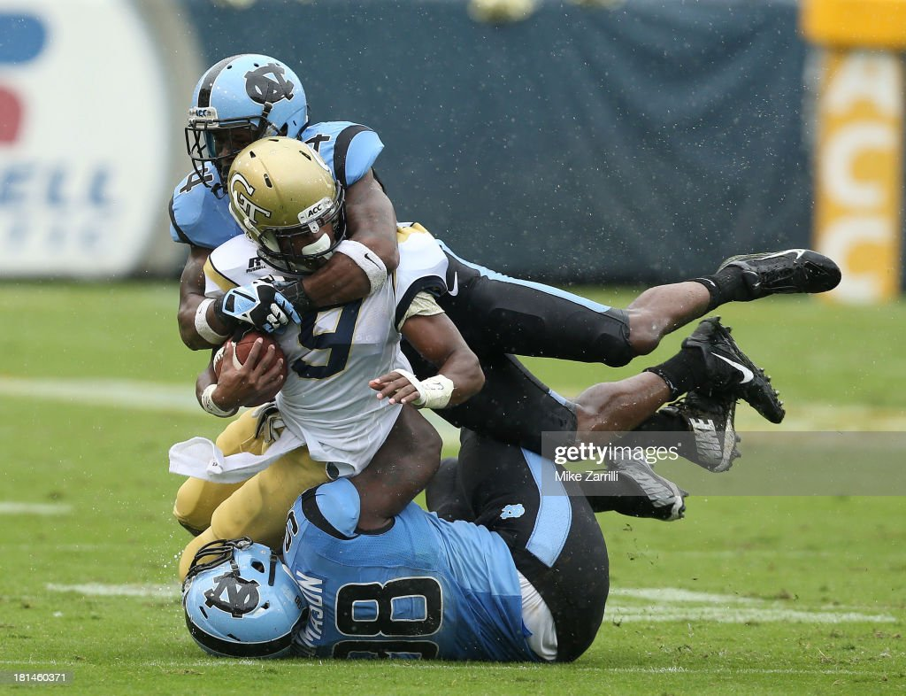 Running back Tony Zenon #9 of the Georgia Tech Yellow Jackets is tackled by safety Jabari Price #4 and defensive tackle Justin Thomason #98 of the North Carolina Tar Heels during the game at Bobby Dodd Stadium at Historic Grant Field on September 21, 2013 in Atlanta, Georgia.