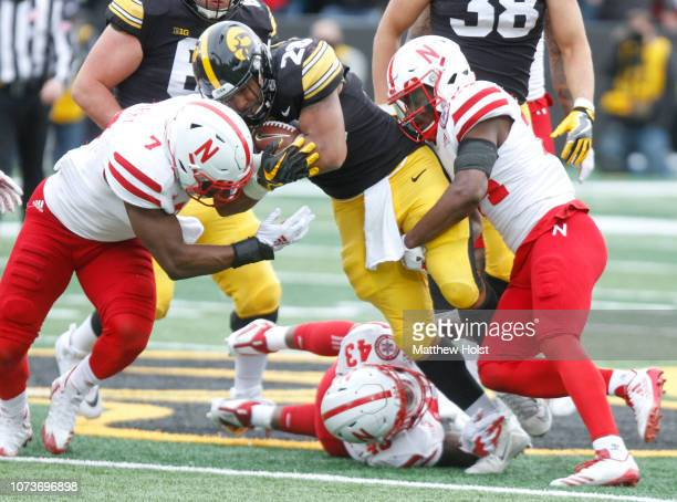Running back Toren Young of the Iowa Hawkeyes is brought down during the first half by linebacker Mohamed Barry and safety Aaron Williams of the...