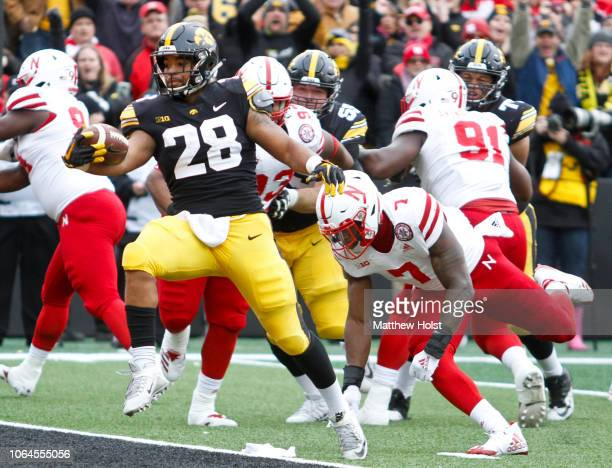 Running back Toren Young of the Iowa Hawkeyes runs in for a touchdown during the first half in front of linebacker Mohamed Barry of the Nebraska...
