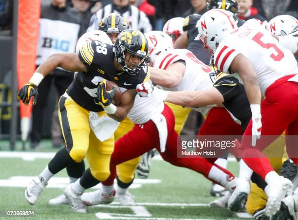 Running back Toren Young of the Iowa Hawkeyes runs up the field during the first half in front of linebacker Mohamed Barry of the Nebraska...