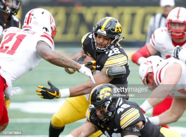 Running back Toren Young of the Iowa Hawkeyes runs up the field during the first half in front of cornerback Lamar Jackson of the Nebraska...