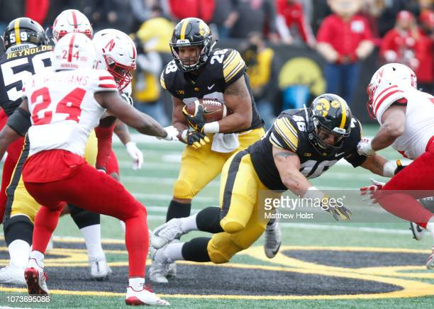 Running back Toren Young of the Iowa Hawkeyes runs up the field during the first half into linebacker Mohamed Barry and safety Aaron Williams of the...