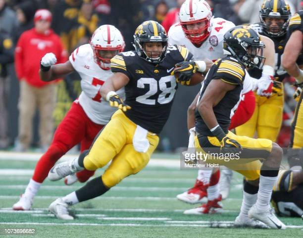 Running back Toren Young of the Iowa Hawkeyes runs up the field during the second half in front of linebacker Mohamed Barry of the Nebraska...