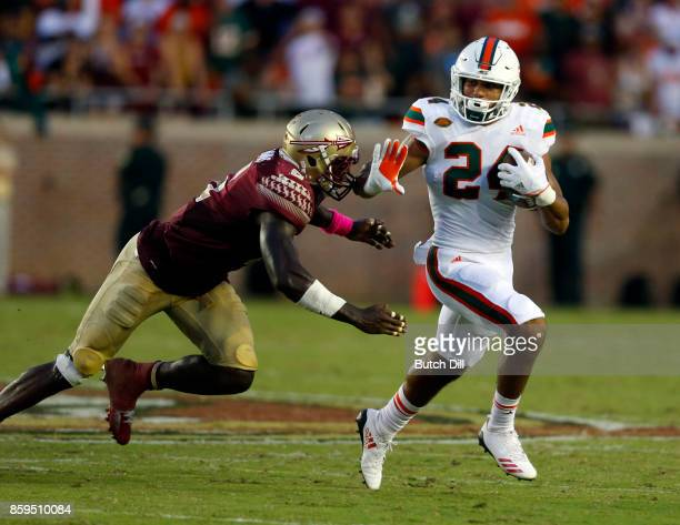 Running back Travis Homer of the Miami Hurricanes tries to get around the tackle of linebacker Matthew Thomas of the Florida State Seminoles during...