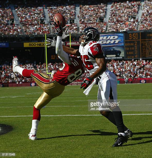 Running back Travis Jervey of the Atlanta Falcons and wide receiver Brandon Lloyd of the San Francisco 49ers attempt to catch a pass during the game...