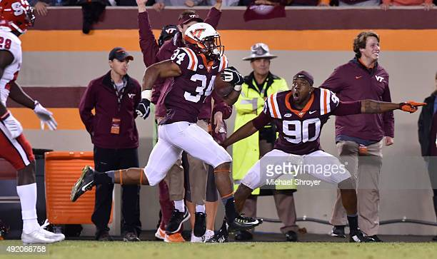 Running back Travon McMillian of the Virginia Tech Hokies carries the ball down the sideline during a long touchdown run against the North Carolina...