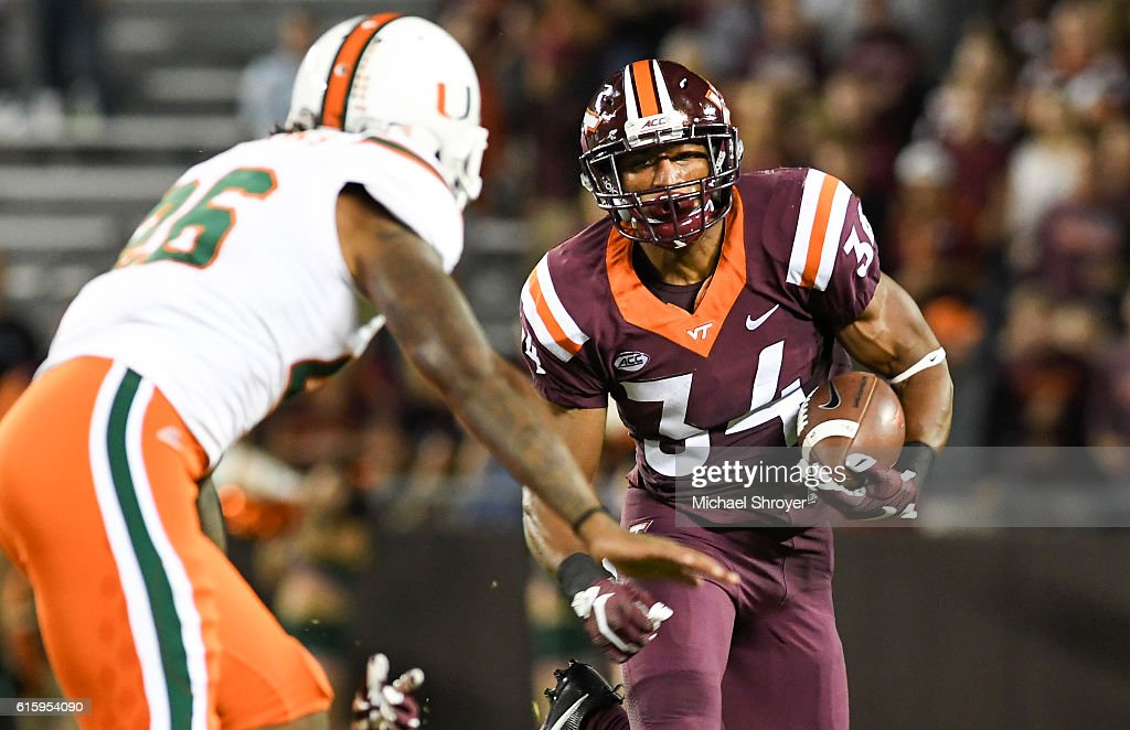 Running back Travon McMillian #34 of the Virginia Tech Hokies carries the ball against the Miami Hurricanes in the first half at Lane Stadium on October 20, 2016 in Blacksburg, Virginia. Virginia Tech defeated Miami 37-16.