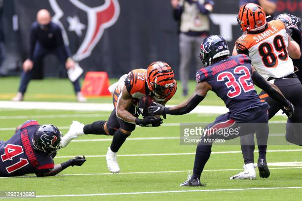 Running back Trayveon Williams of the Cincinnati Bengals carries the foot ball against the defense of inside linebacker Zach Cunningham and...