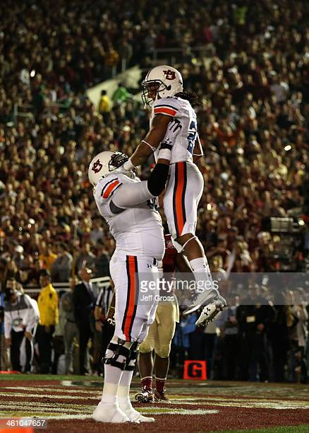Running back Tre Mason of the Auburn Tigers celebrates with offensive linesman Chad Slade after a 12yard touchdown against the Florida State...