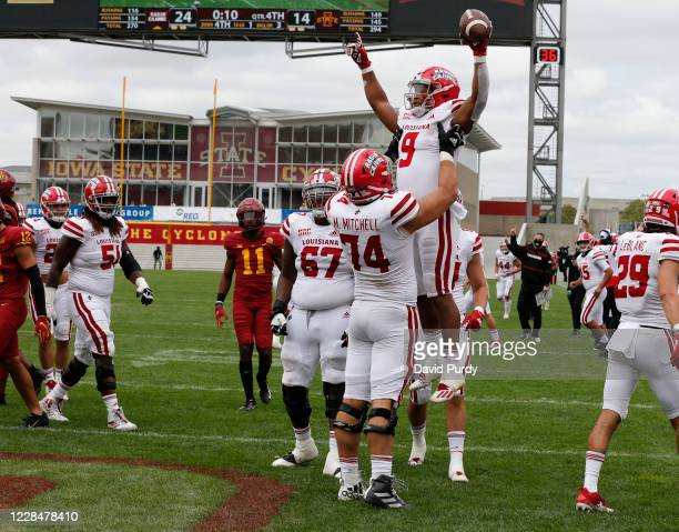 Running back Trey Ragas of the Louisiana-Lafayette Ragin Cajuns is lifted into the air by teammate offensive lineman Max Mitchell of the...