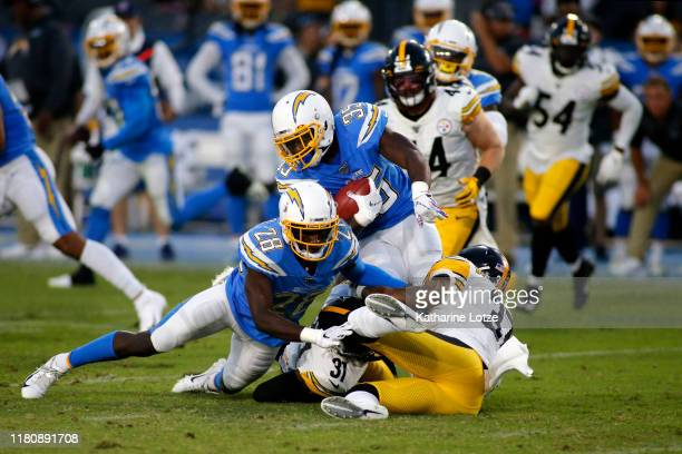 Running back Troymaine Pope of the Los Angeles Chargers is tackled by cornerback Justin Layne and defensive back Jordan Dangerfield of the Pittsburgh...