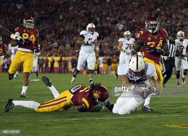 Running back Tyler Gaffney of the Stanford Cardinal dives into the endzone for a touchdown while being tackled by Josh Shaw of the USC Trojans in the...