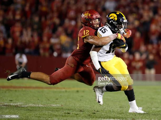 Running back Tyler Goodson of the Iowa Hawkeyes is tackled by defensive back Greg Eisworth of the Iowa State Cyclones as he rushed for yards in the...