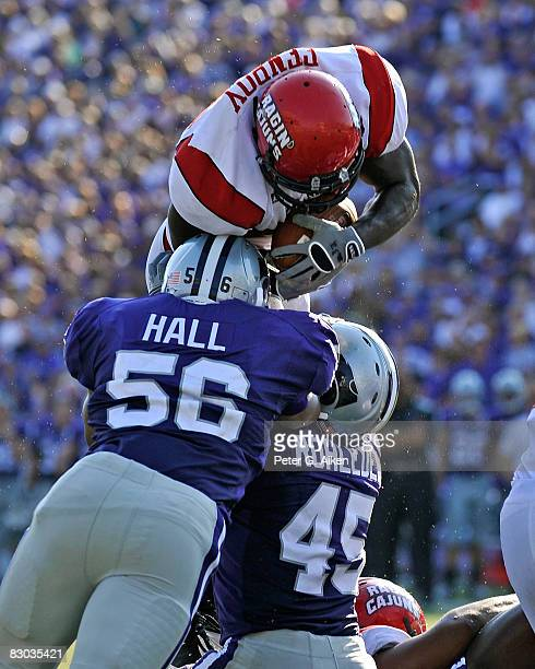 Running back Tyrell Fenroy of the Louisiana-Lafayette Ragin' Cajuns tries to dive over the top of linebackers Olu Hall and Kevin Rohleder of the...