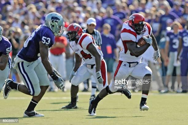 Running back Tyrell Fenroy of the Louisiana-Lafayette Ragin' Cajuns rushes up field in the third quarter past linebacker Reggie Walker of the Kansas...