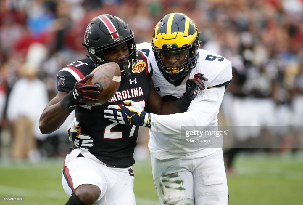 Running back Ty'Son Williams #27 of the South Carolina Gamecocks is stopped by linebacker Mike McCray #9 of the Michigan Wolverines during the second quarter of the Outback Bowl NCAA college football game on January 1, 2018 at Raymond James Stadium in Tampa, Florida.