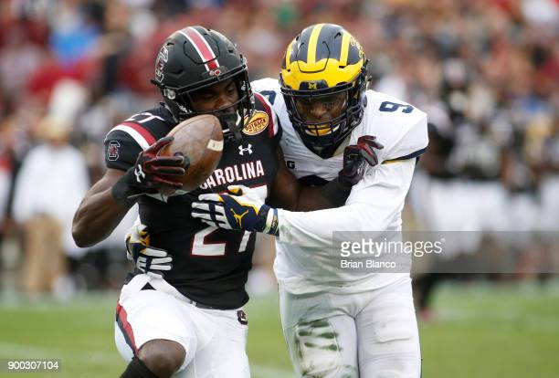Running back Ty'Son Williams of the South Carolina Gamecocks is stopped by linebacker Mike McCray of the Michigan Wolverines during the second...