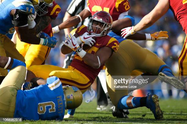Running back Vavae Malepeai of the USC Trojans is tackled by defensive back Adarius Pickett of the UCLA Bruins during the second half of a football...