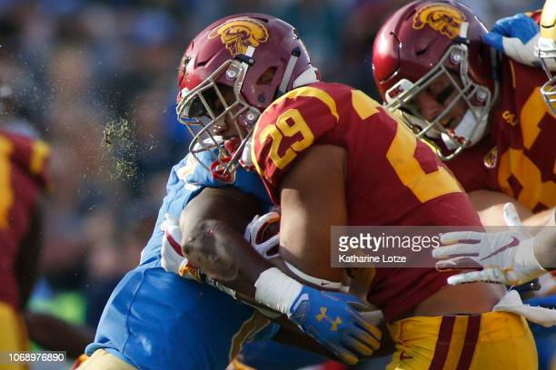 Running back Vavae Malepeai of the USC Trojans pushes forward through a tackle during the second half of a football game at Rose Bowl on November 17...