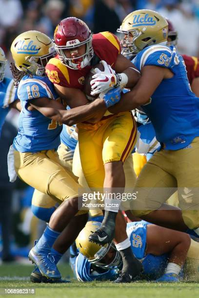 Running back Vavae Malepeai of the USC Trojans pushes through a tackle by defensive back Elijah Gates of the UCLA Bruins and defensive lineman Tyler...