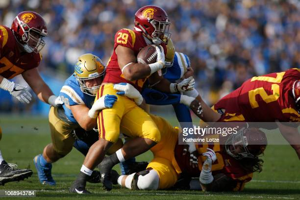 Running back Vavae Malepeai of the USC Trojans tries to break through a tackle during during the first half of a football game at Rose Bowl on...