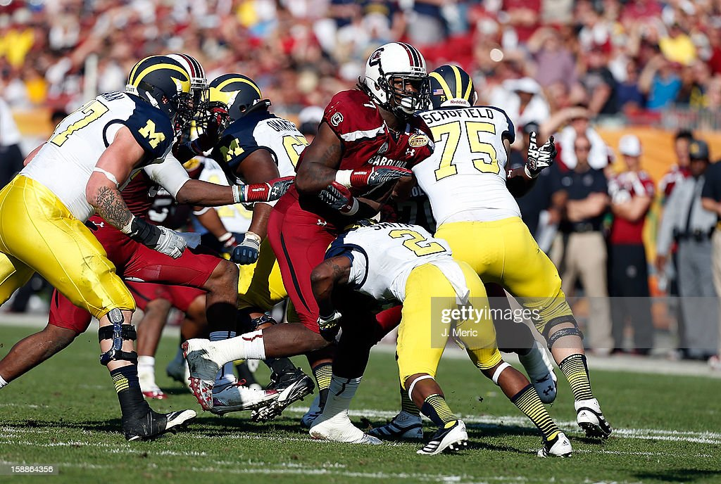 Running back Vincent Smith #2 of the Michigan Wolverines blocks defensive end Jadeveon Clowney #7 of the South Carolina Gamecocks during the Outback Bowl Game at Raymond James Stadium on January 1, 2013 in Tampa, Florida.