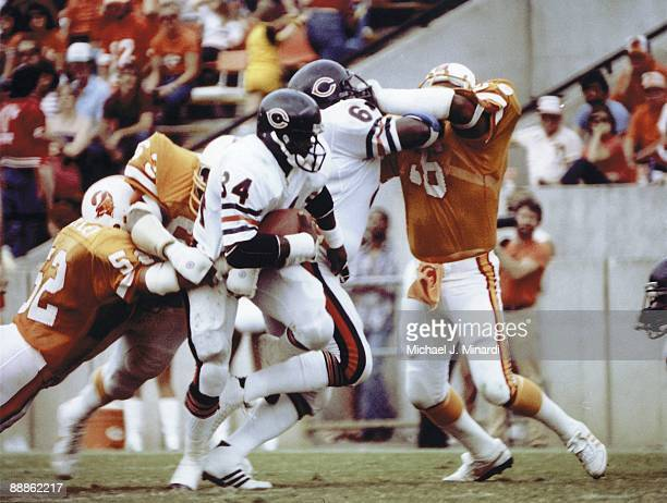 Running back Walter Payton of the Chicago Bears carries the ball against Scot Brantley and LB Hugh Green of the Tampa Bay Buccaneers on October 6...