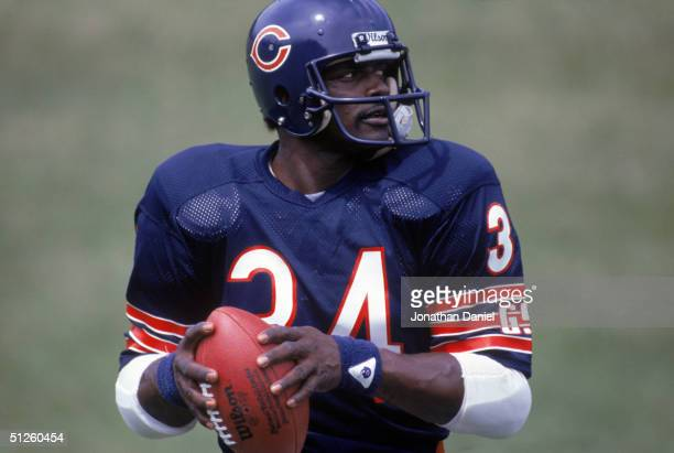 Running back Walter Payton of the Chicago Bears looks on to pass during training camp in 1985