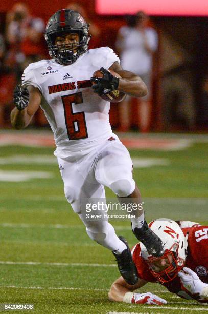 Running back Warren Wand of the Arkansas State Red Wolves slips the tackle of linebacker Luke Gifford of the Nebraska Cornhuskers at Memorial Stadium...