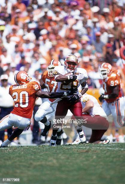 Running back Warrick Dunn of the Florida State Seminoles runs with the ball as Brian Dawkins of the Clemson Tigers goes for the tackle on September 9...