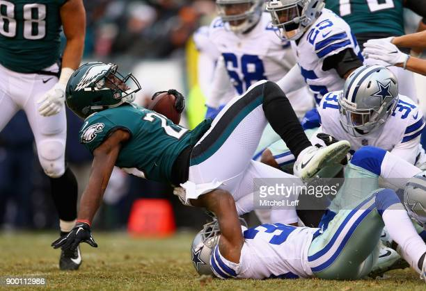 Running back Wendell Smallwood of the Philadelphia Eagles is tackled by cornerback Chidobe Awuzie and free safety Byron Jones of the Dallas Cowboys...