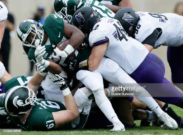 Running back Weston Bridges of the Michigan State Spartans is tackled by linebacker Paddy Fisher of the Northwestern Wildcats during the first half...